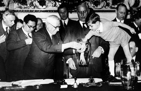 World Cup Finals, 1938. Paris, France. FIFA president Jules Rimet is assisted by a young boy in making the draw for the World Cup.