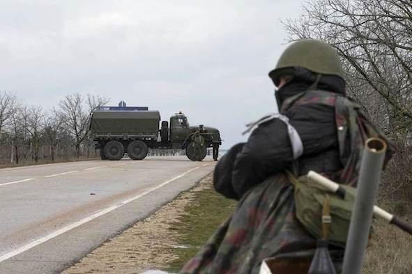 An armed man stands guard at the entrance to Belbek Airport in the Crimea region